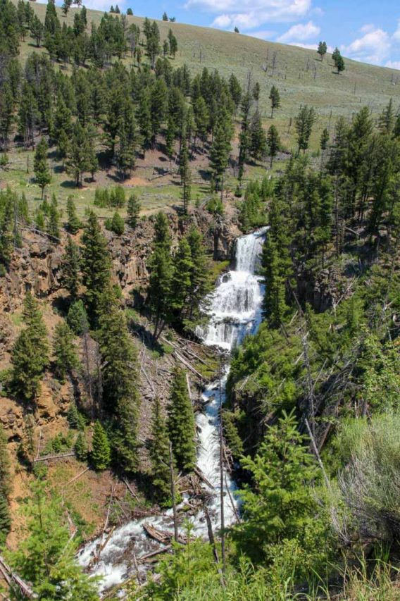 Waterfall cascading down hillside with pine trees and blue sky