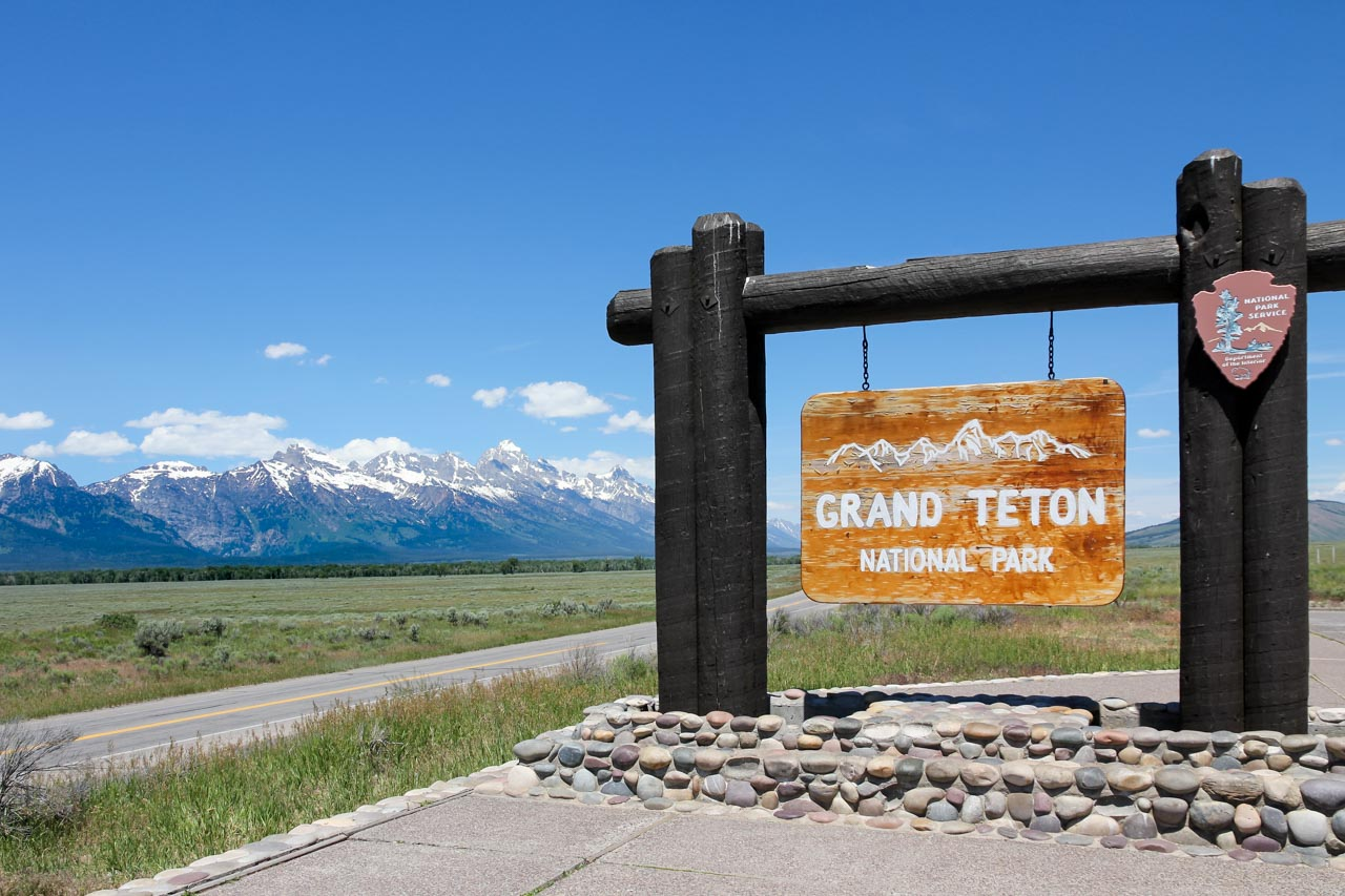 """Grand, wooden sign reading """"Grand Teton National Park"""" with mountains in the background"""