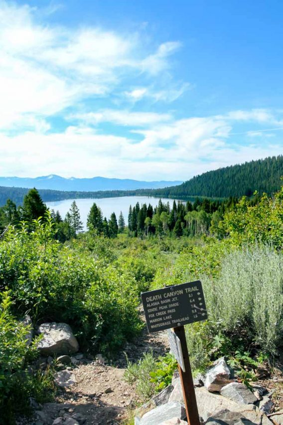Trail sign for Death Canyon with Lake and mountains in the background
