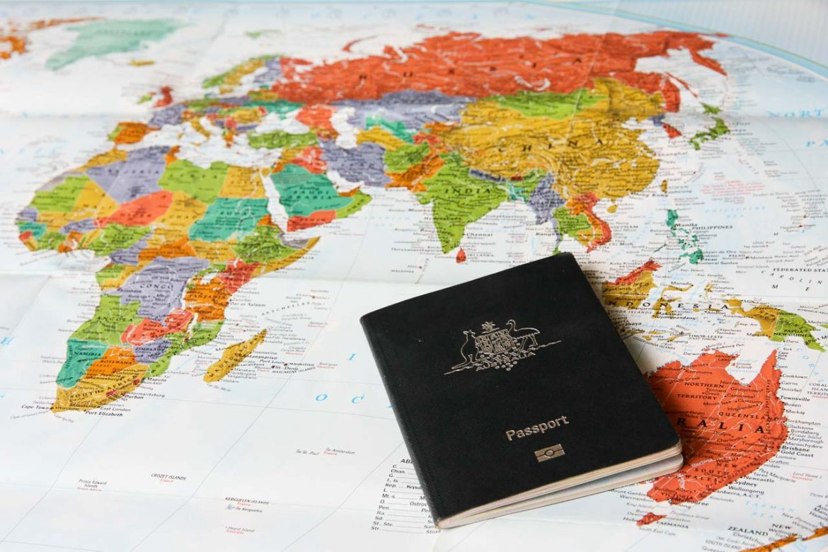 Image of colourful world map with Australian passport placed on top