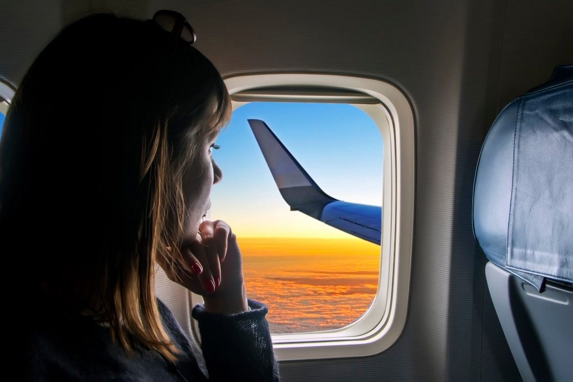 Woman looking out plane window at sunset