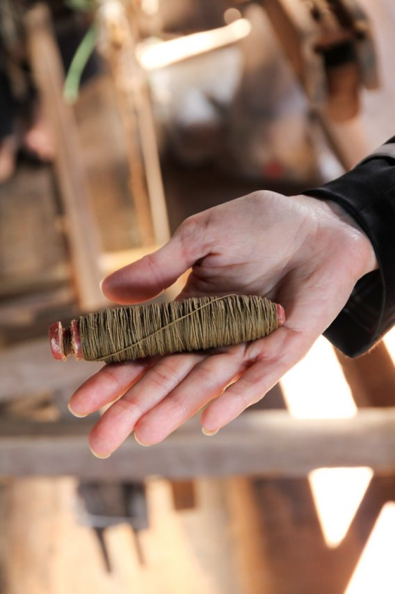 A woman's hand holding a spool of undyed lotus thread
