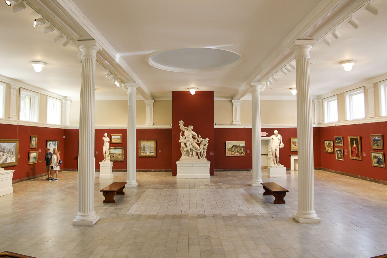 Art museum space with tiled floor, with red walls and white ceiling
