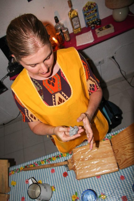 Woman in yellow apron rolling tortilla dough over a wooden press