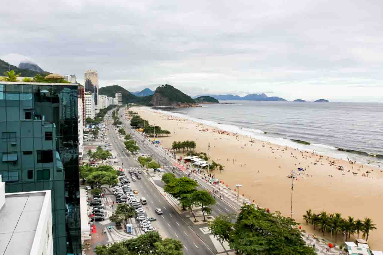 Rooftop view of beach looking north to mountains, with street and mosaic Rio sidewalks below