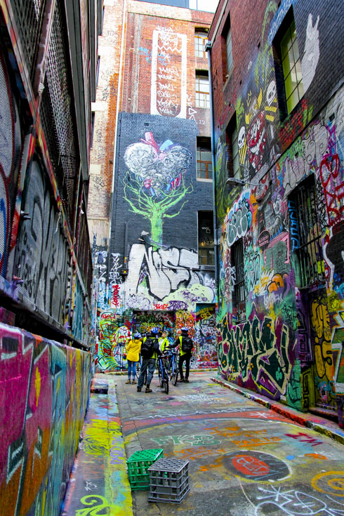 People with bikes touring street art in a colourful Melbourne Laneway