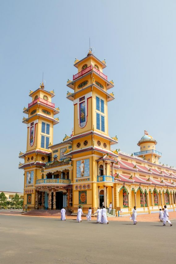 People all in white approaching ornate yellow religious building.