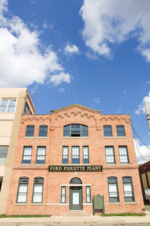 Red brick exterior of old 3-story building with black and gold sign reading - Ford Piquette Plant