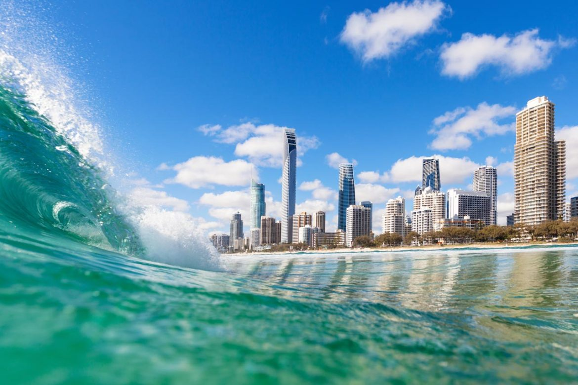 Image of wave crashing with city skyline in background