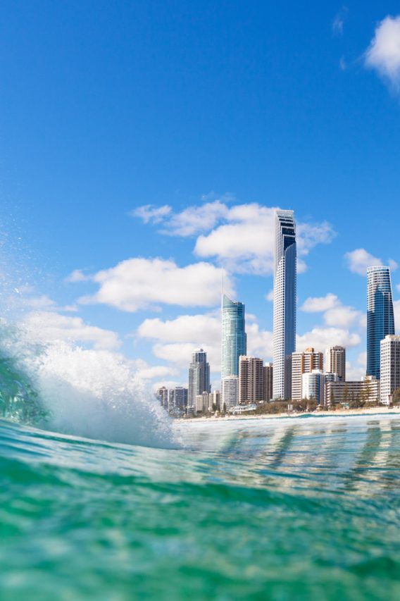 Gold Coast skyline from the water with creashing wave in foreground