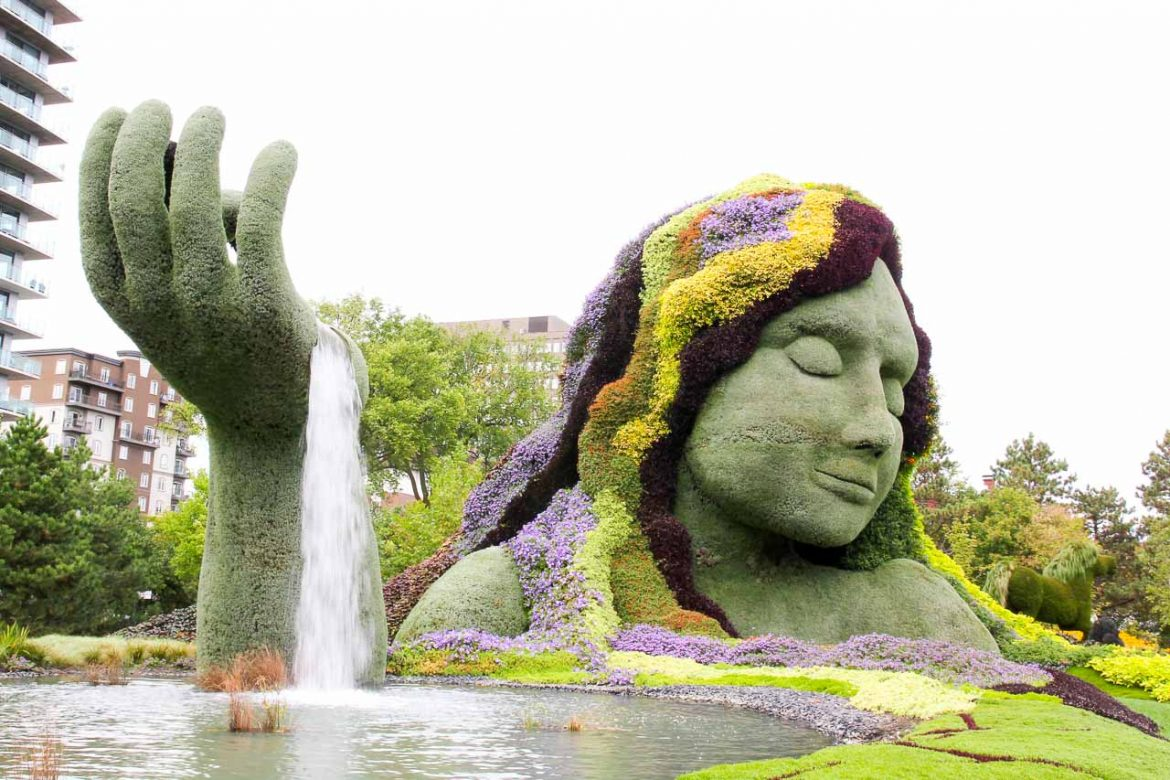 Living sculpture of Mother Earth holding up one hand with water running out into a pond