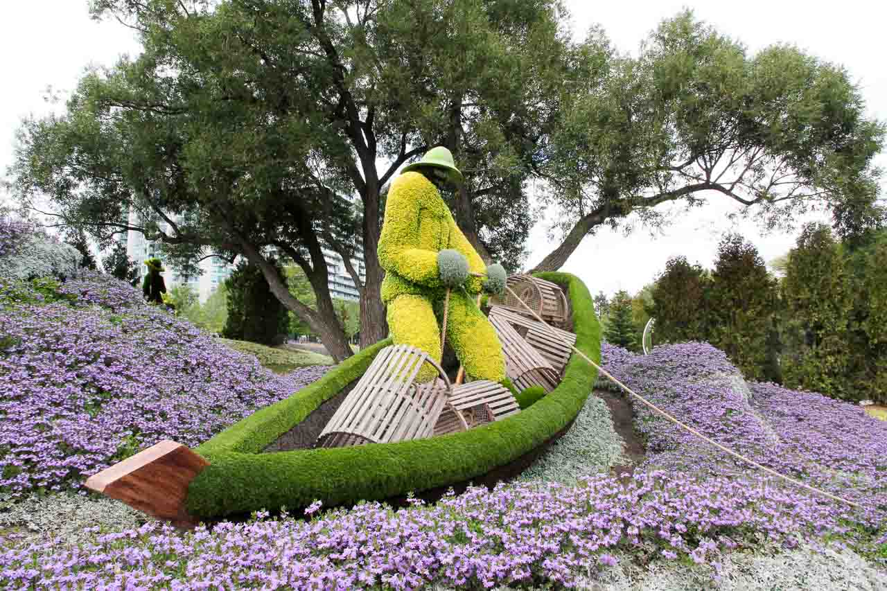 Living sculpture of a lobster fisherman in a boat, on a see of purple flowers