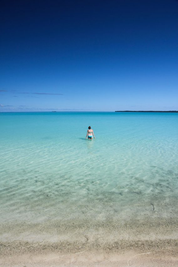 Woman wading into crystaline, blue waters with blue sky