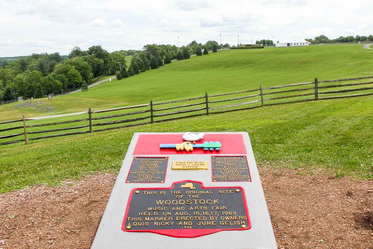 Photo of the Woodstock festival marker overlooking the field where the event was held