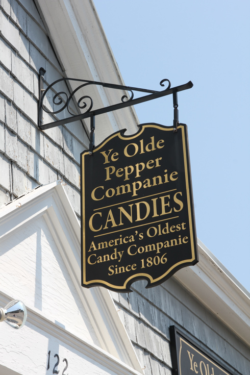 """Old fashioned hanging sign outside of shop reading """"Ye Olde Pepper Companie Candies - America's Oldest Candy Companie Since 1806"""
