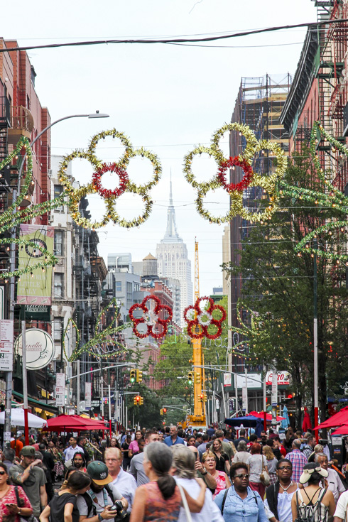 People filled street of Little Italy with Empire State Building in distance