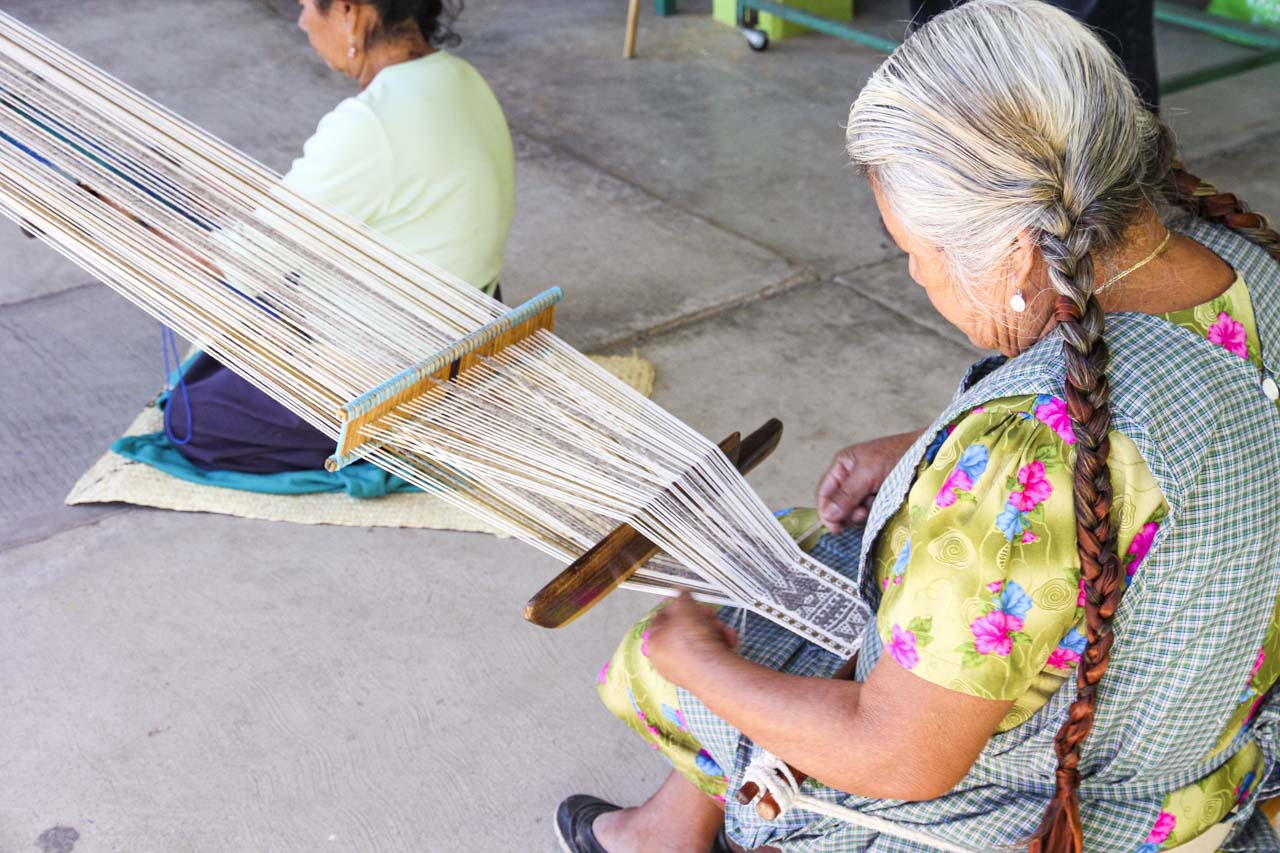Ladies weaving cotton on a backstrap loom