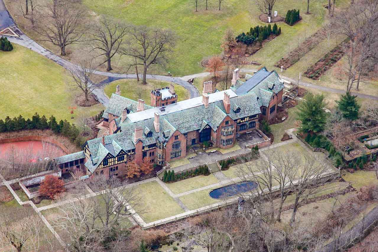 Aerial photo of large Tudor Revival mansion and gardens in early spring