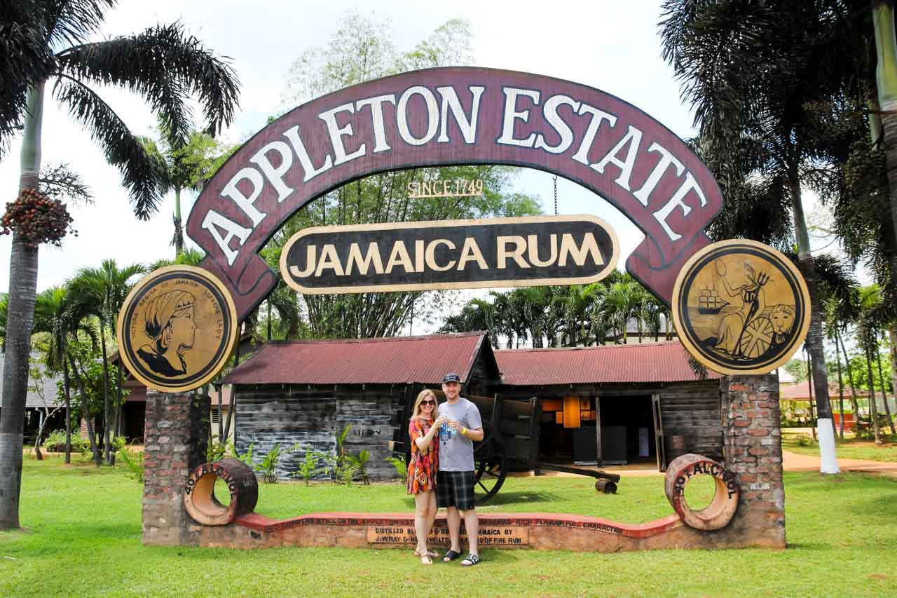 Couple saying cheers over rum cocktails under an outdoor Appleston Estate Jamaica Rum sign