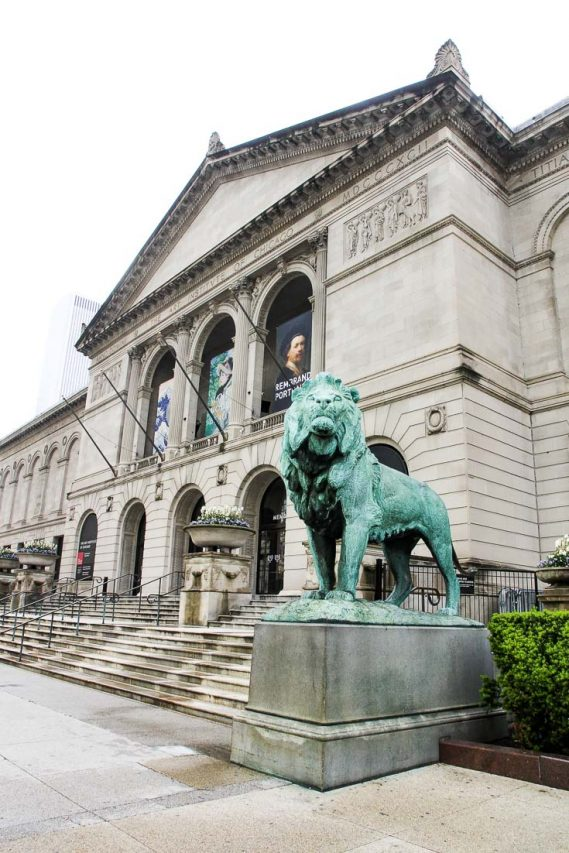 Exterior entrance of the Chicago Art Institute with lion sculpture in foreground