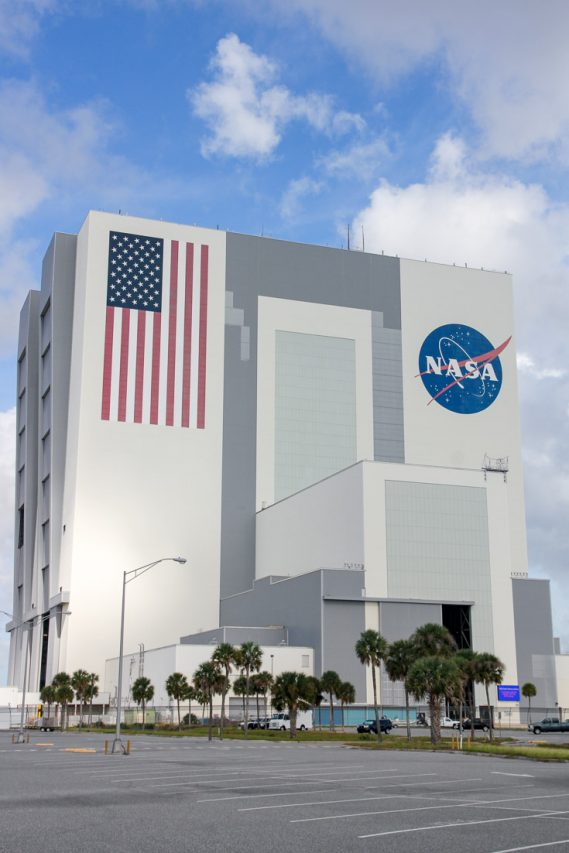 Exterior of the Vehicle Assembly Building with NASA badge and US flag painted on the side
