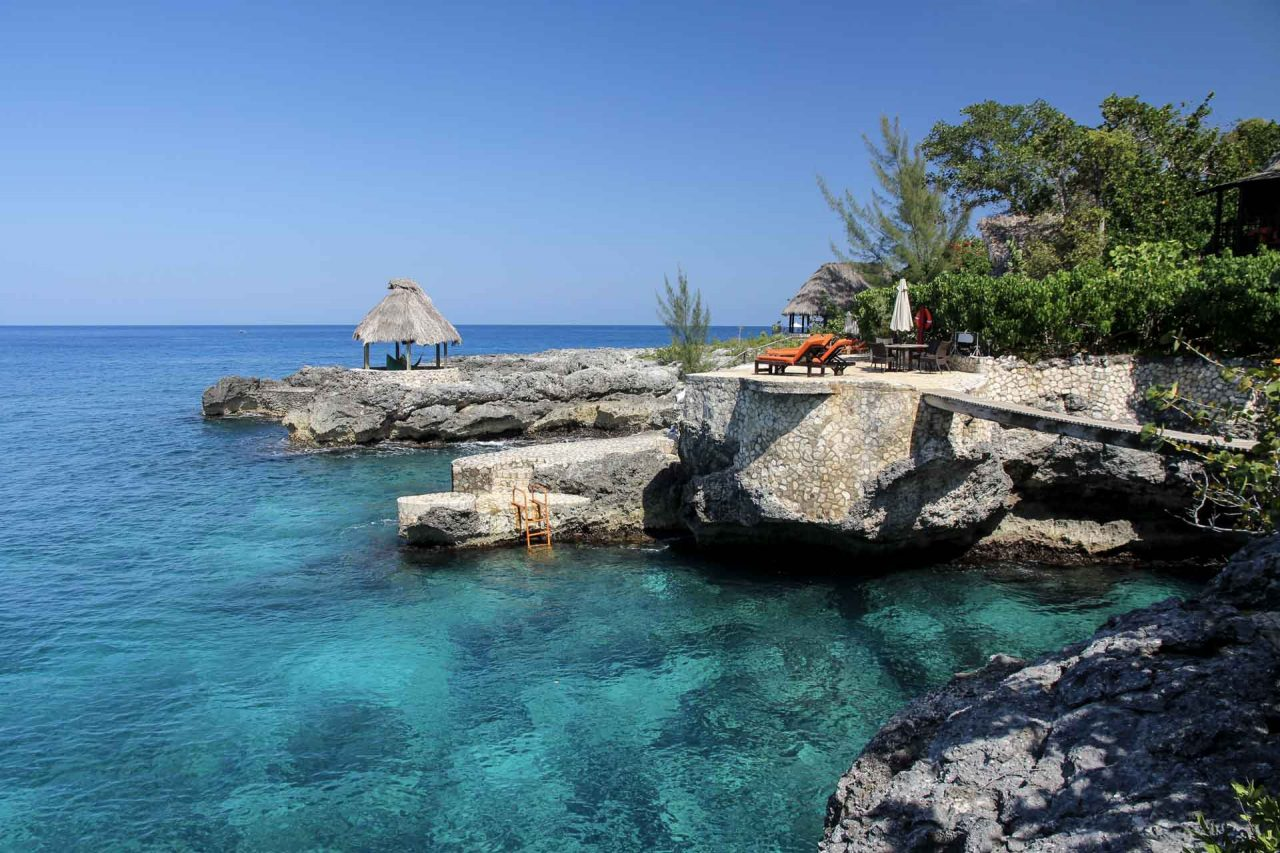 Negril's azure waters and cliffed coastline with orange sun lounges and a tiki hut
