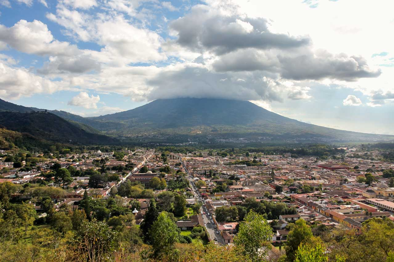 Clouds resting on Volcán de Agua in background with the city of Antigua in foreground
