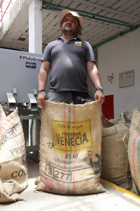 Man holding sack of coffee beans