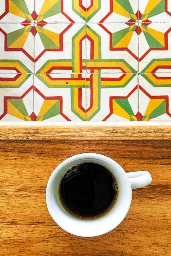 Coffee cup on wooden table with red yellow and green patterned floor tiles below