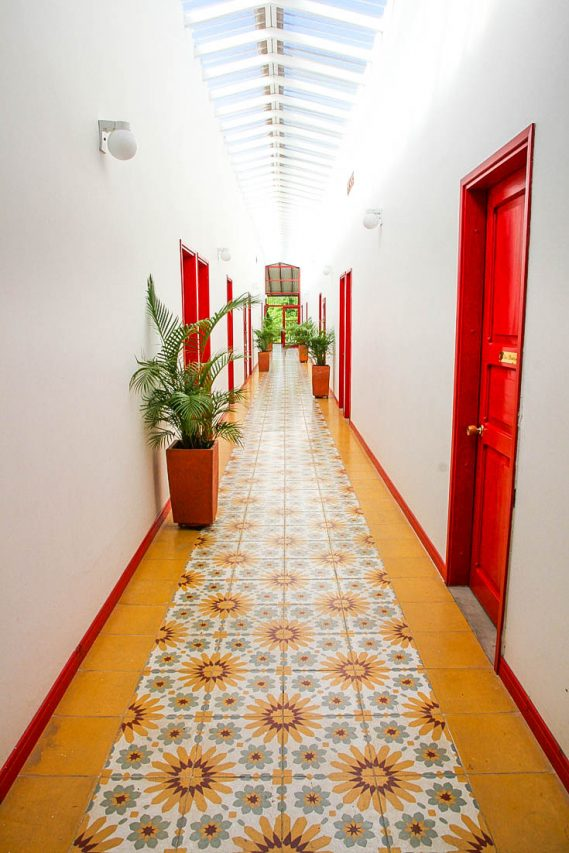 Naturally lit corridor with coloured tiles, red doorways and potted palm trees