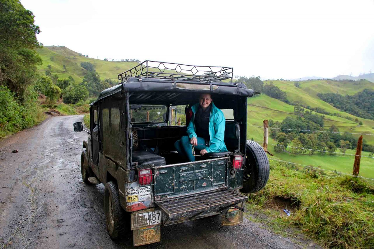 Woman in the back of Jeep on a wet road, in green rural landscape