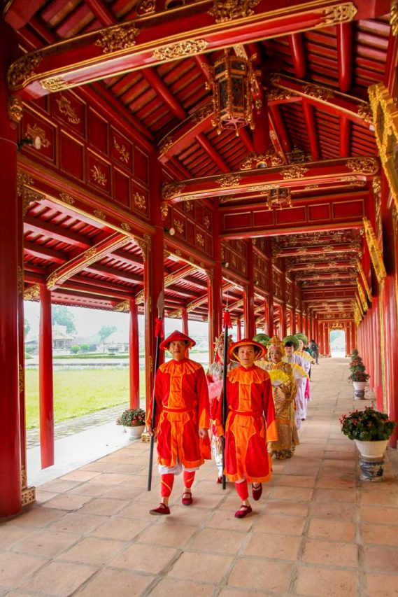 People dressed in traditional Vietnamese ceremonial clothing, parading down red and gold colonnade.