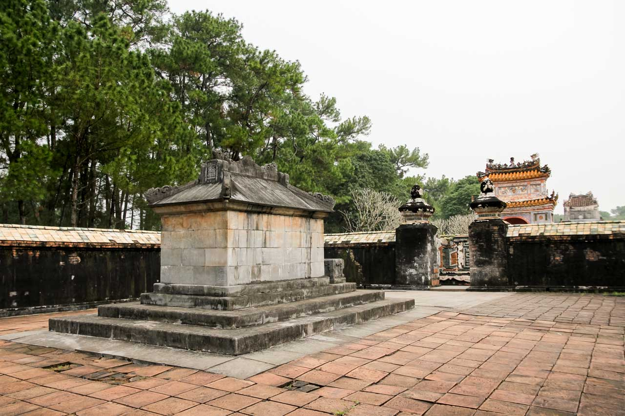 Photo of Tu Duc Tomb with walls and decorative gate in background.