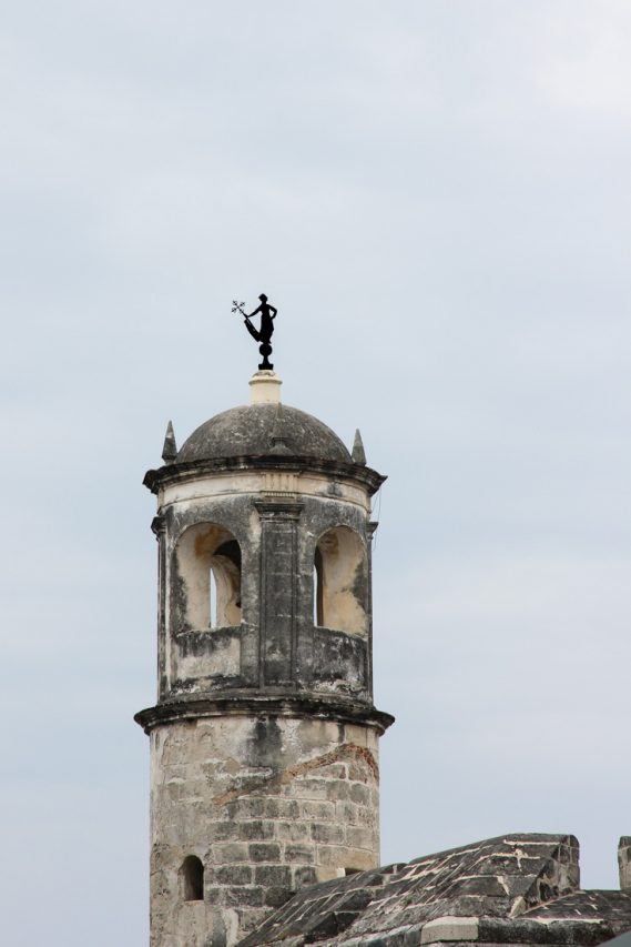 Weather vane in shape of woman holding cross on top of stone tower