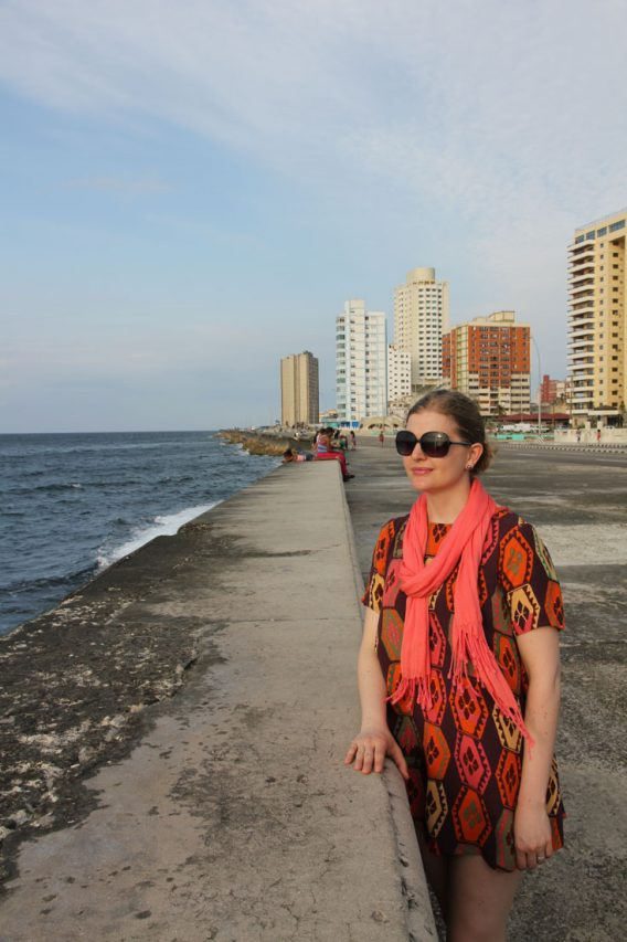 Woman in orange toned dress standing at sea wall with highrise buildings in the background