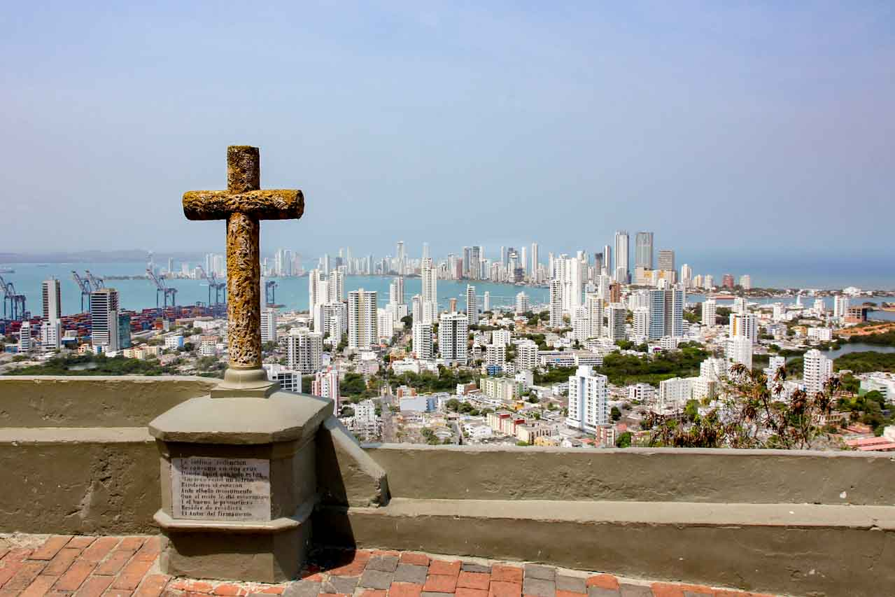Panoramic view of city below with cross in foreground