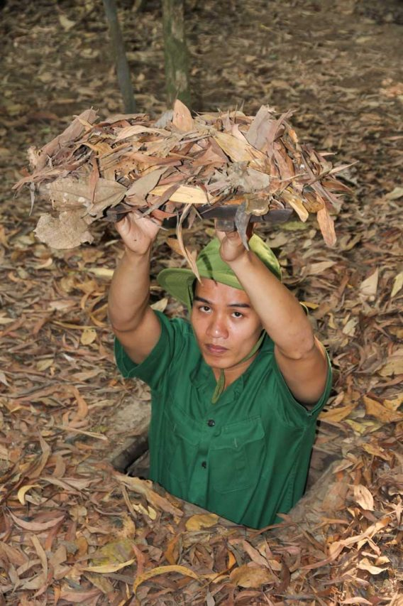 Man in army greens demonstrating strap door disguised by leaf litter.
