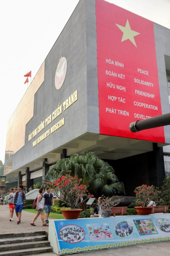 Red banner with yellow star down side of large rectangular, concrete building with gold lettering.