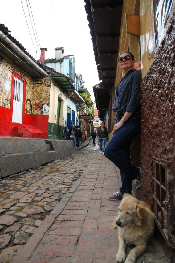 Woman and dog in narrow cobblestone street