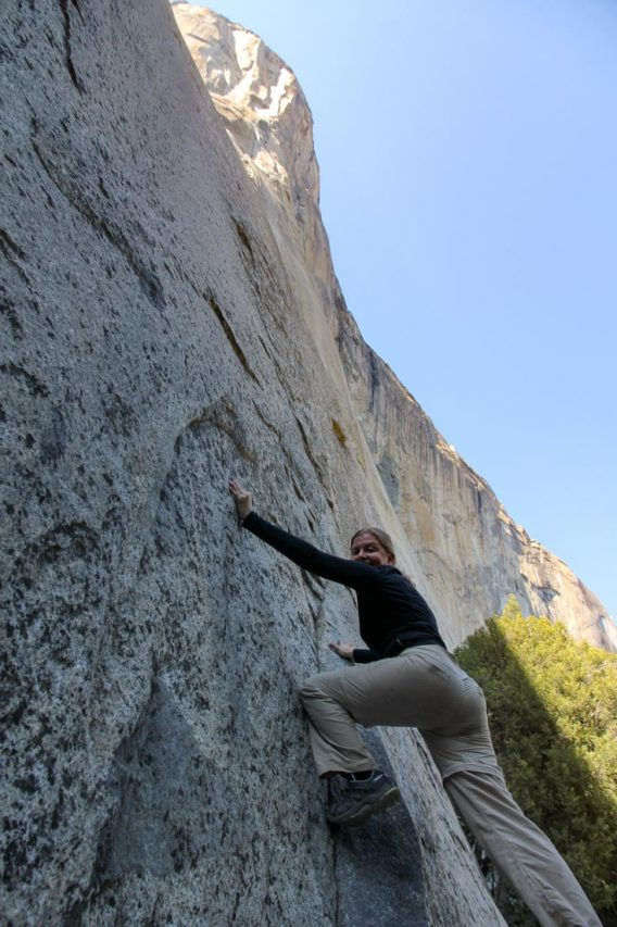 Woman climbing granite cliff with blue sky above