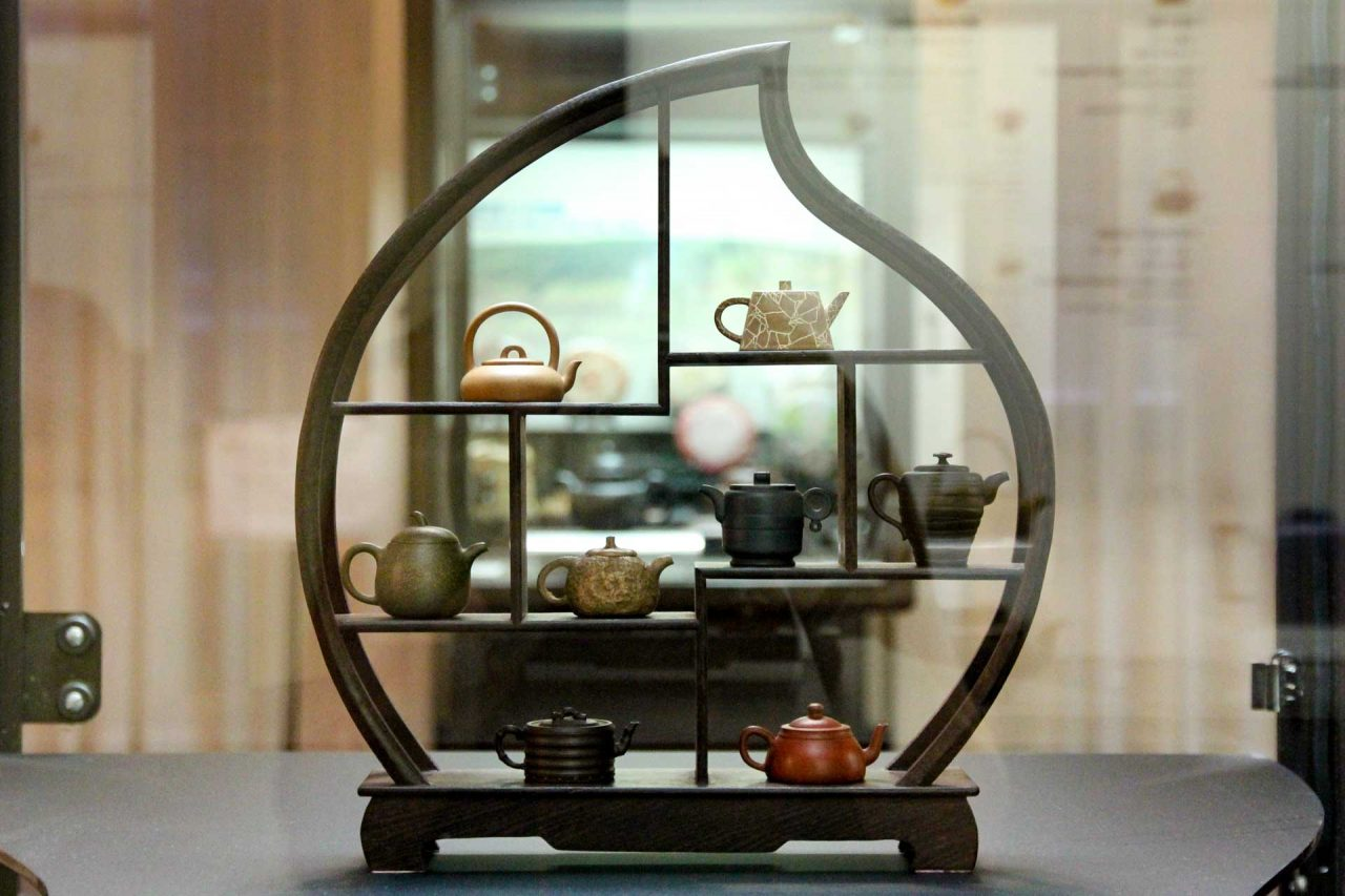 A geometric wooden stand with tiny teapots on shelves