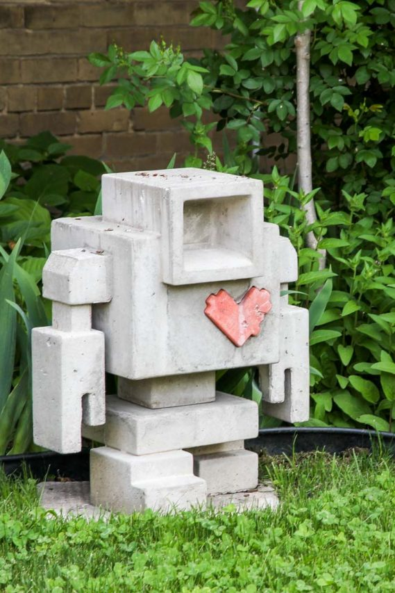 Concrete sculpture of a robot with a red heart on its chest, standing in a garden