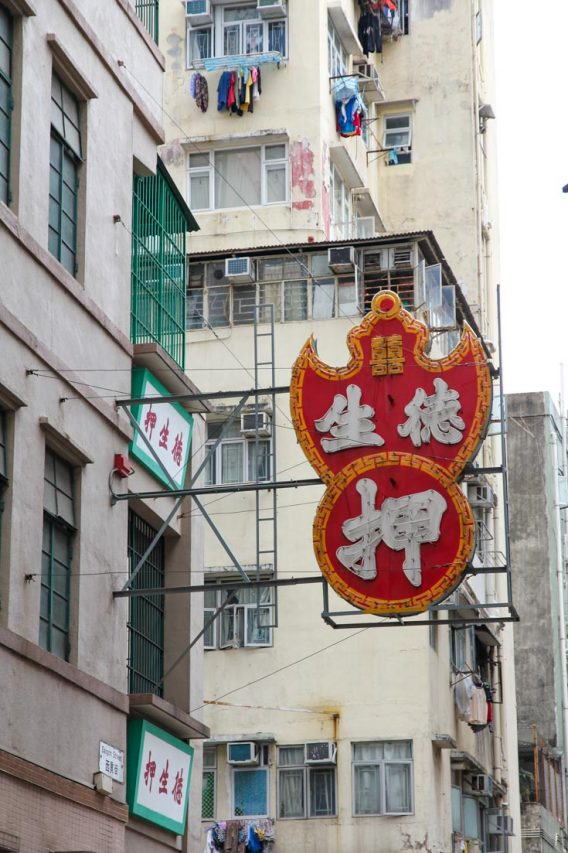 Red bat shaped sign with Chinese script, attached to high rise building