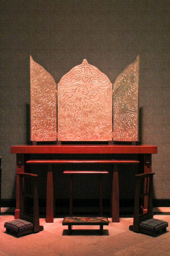 Gold triptych with engravings in Keith Haring's characteristic style, on red alter.