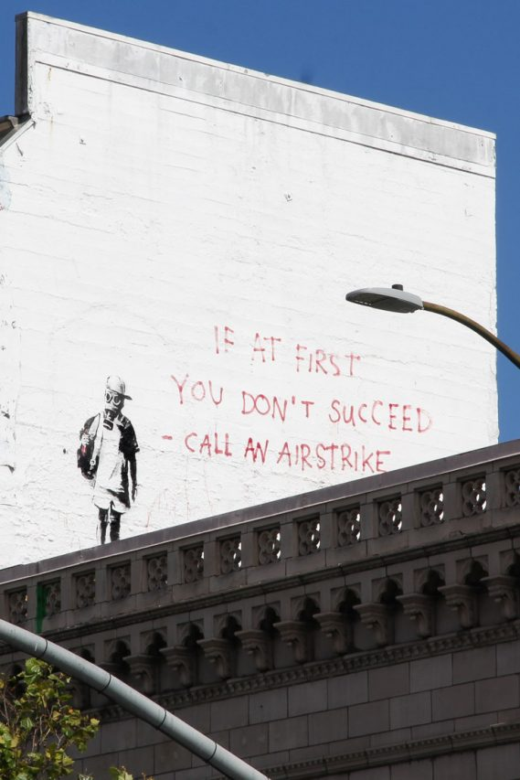 """Street at painted on white wall depicting young boy in gas mask and text reading """"if at first you don't succeed - call an airstrike"""""""