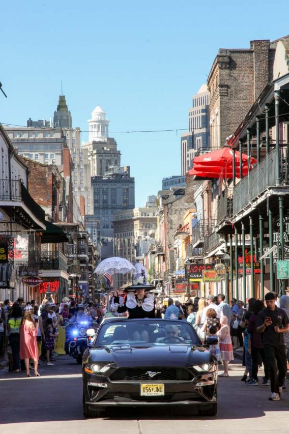 Black car driving up busy Bourbon St with lady in Easter Bonnet and holding a parasol