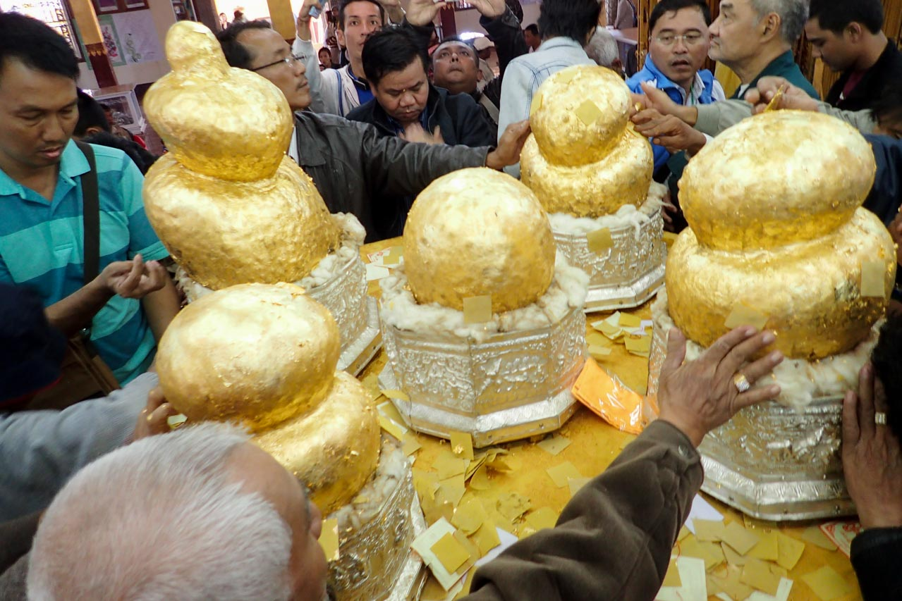 Men jostling over gold leaf covered Buddha images