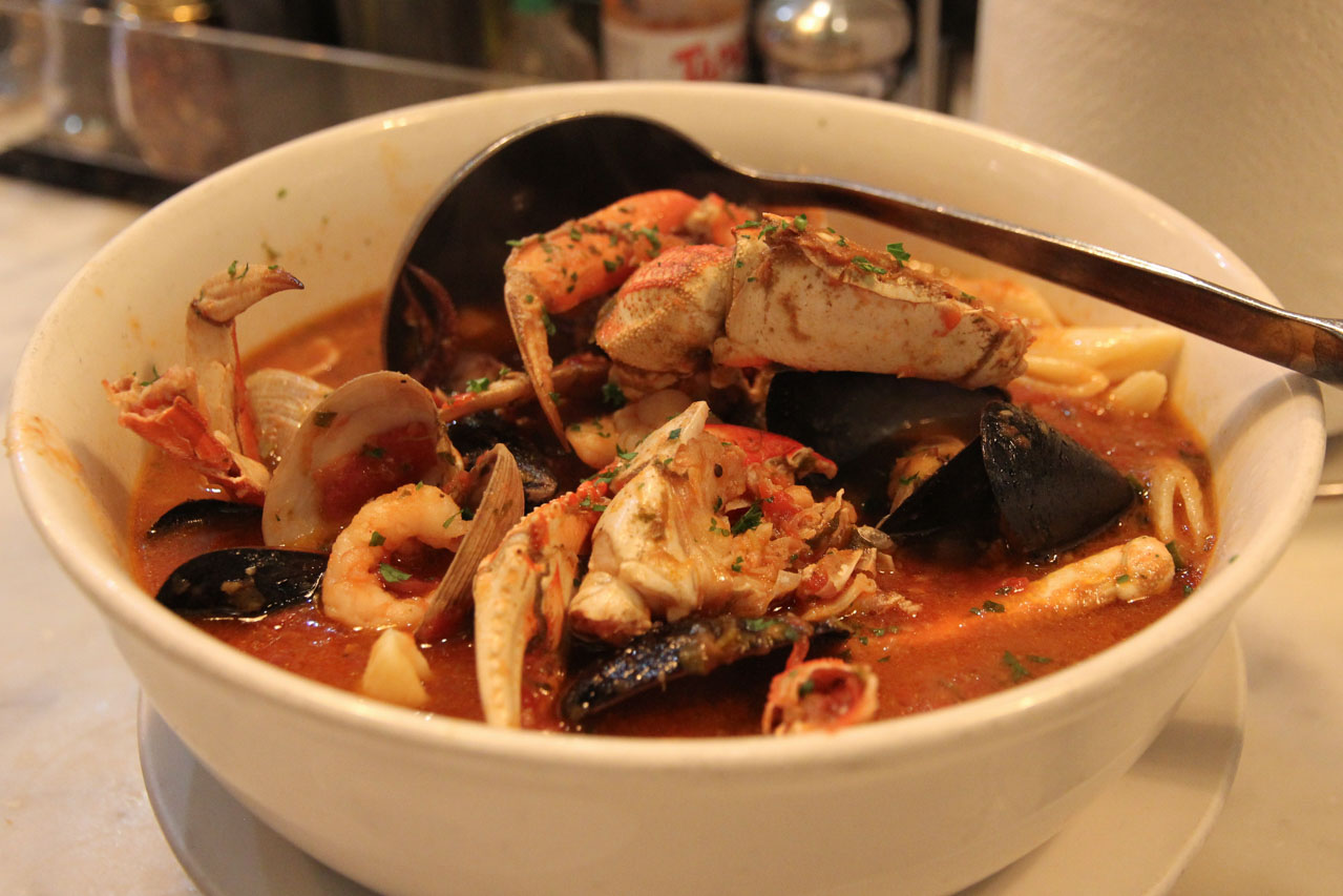 White bowl of seafood in tomato red broth with laddle
