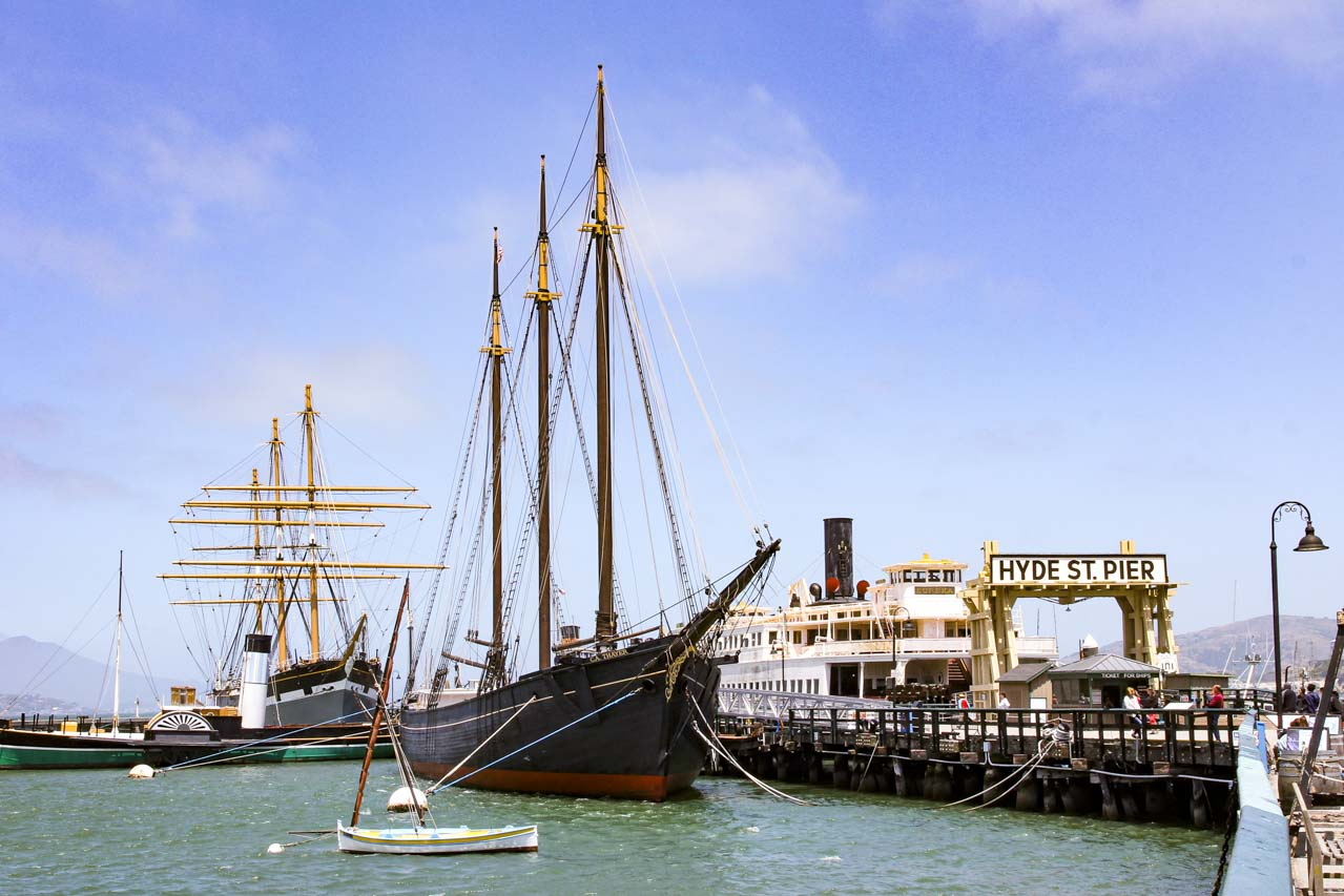 Historic ships moored at pier with sign reading Hyde St Pier