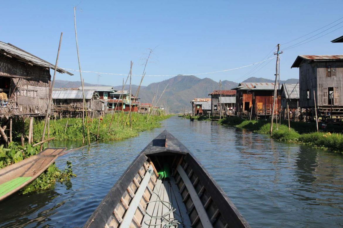 Bow of boat with stilted houses on Lake in foreground and mountains in background
